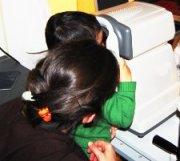 Controllo oculistico di bambino con madre